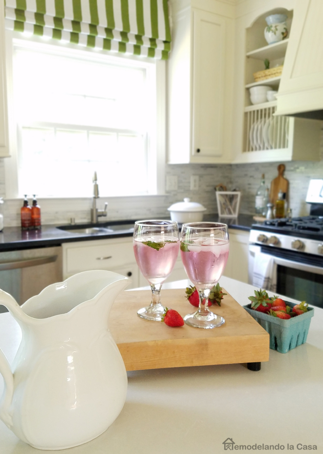 white pitcher with lemonade, strawberries inside blue carton pail, white cabinets