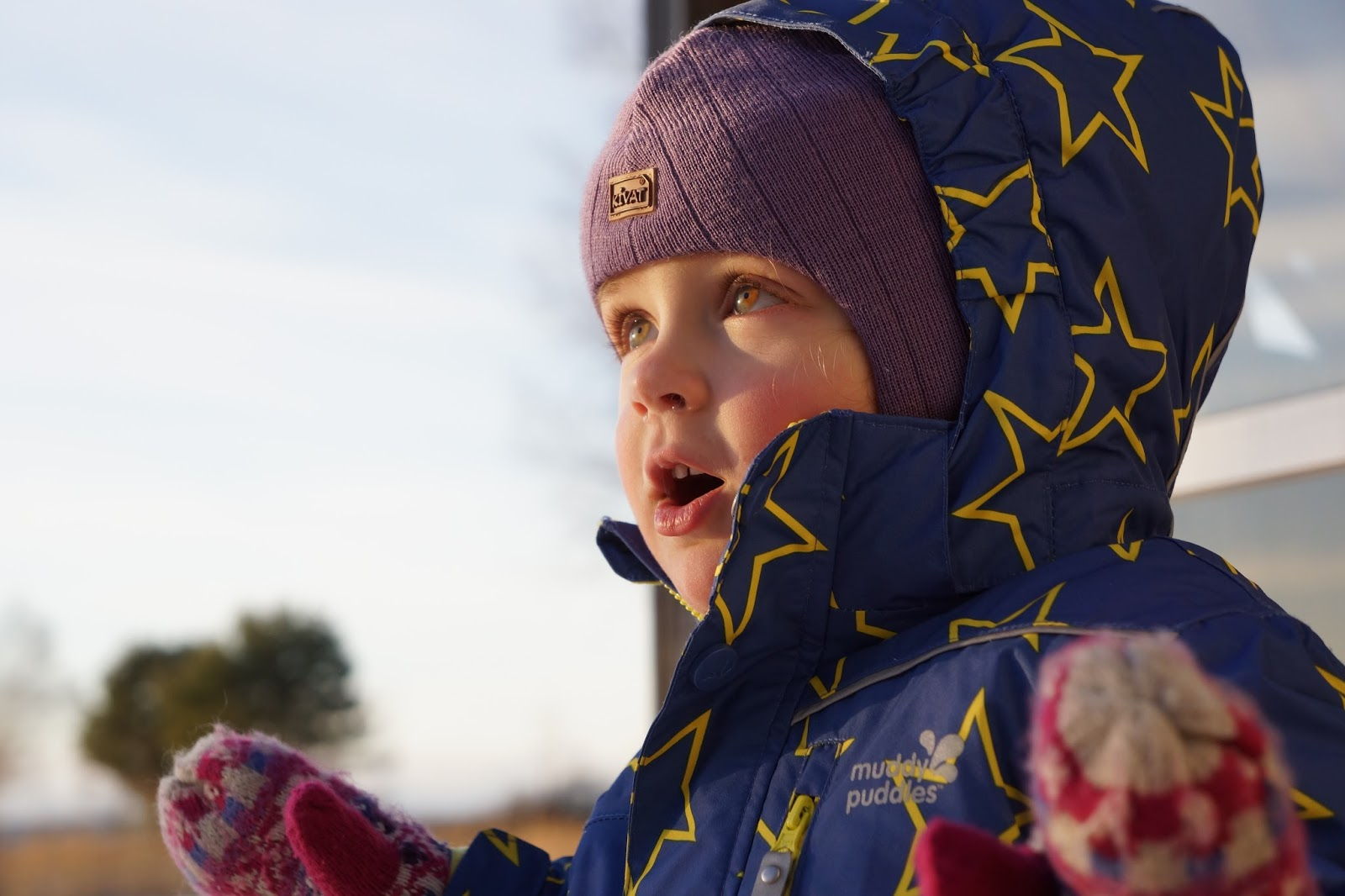 a child wearing ski clothing and playing out in freezing weather