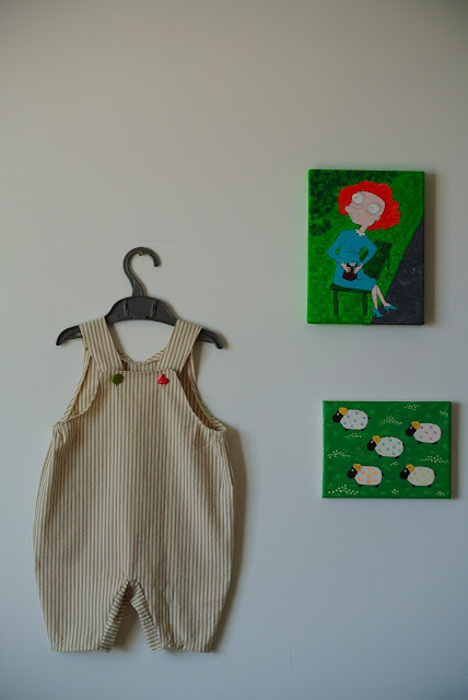 cute baby romper and paintings on wall