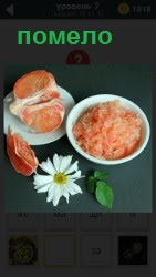 Цитрусовый плод помело очищен на тарелке и порезан на дольки, рядом лежит ромашка