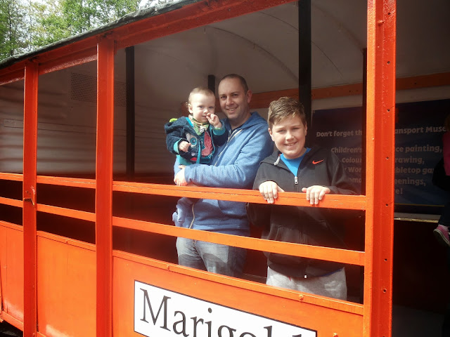 Man holding a baby and a young boy standing on board a carriage