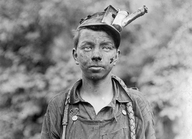 A young driver in the Brown Mine in Brown, West Virginia, in September of 1908. He had been driving pack animals for one year, working from 7 a.m. to 5:30 p.m. daily. The device attached to his cap is an oil-wick cap lamp, which would be lit when the boy was working in the mine tunnels.