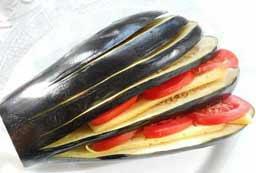 Между полосками баклажанов положить по 2-3 кружочка помидора и по 2 ломтика сыра.
