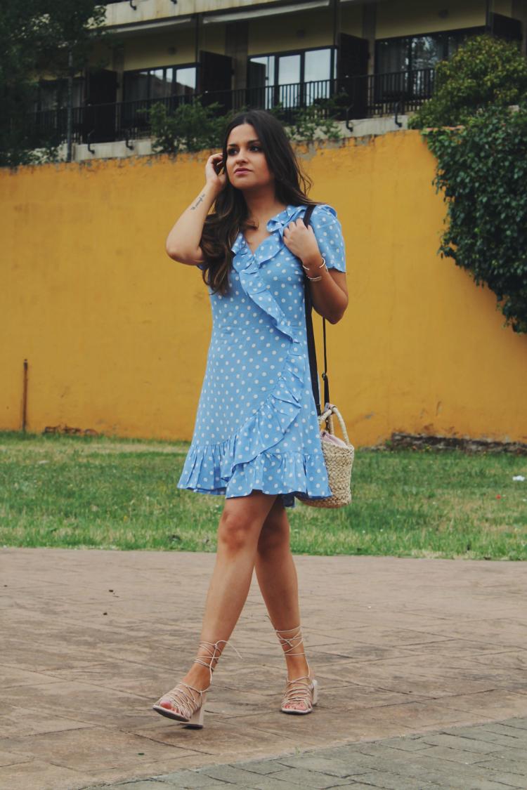 Look de moda con vestido de volantes y bolso de rafia