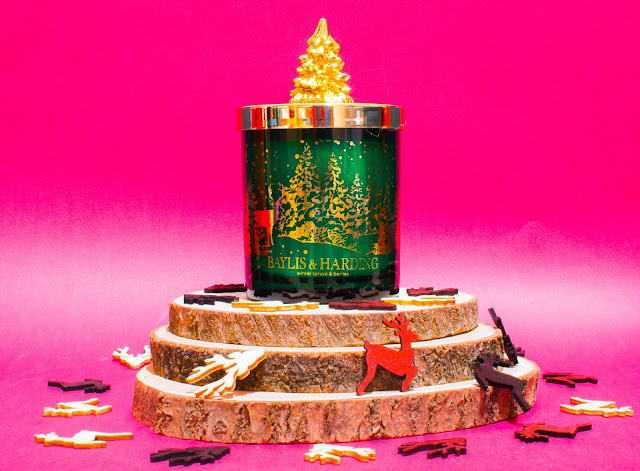A candle in a green glass sjar with gold trees on and gold lid with a tree on and sitting on cut wood rounds with christmassy wooden confetti