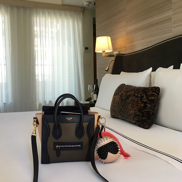Celine Tricolor Taupe Olive and Anthracite Nano bag with Fendi Karlito Karl Lagerfeld bag bug charm, atop a bed at The Quin hotel
