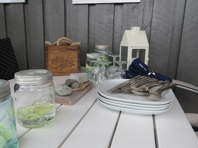 Spisekroken med dekketøy og orkideer i norgesglass på hytteverandaen