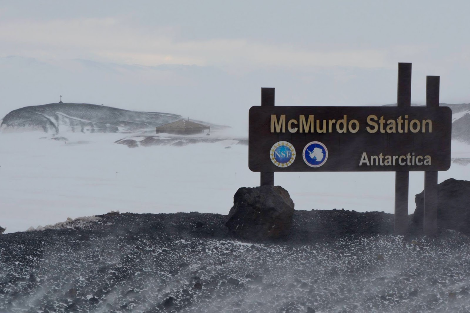 """A sign saying """" McMurdo Station, Antarctica"""" overlooking snowy mountains"""