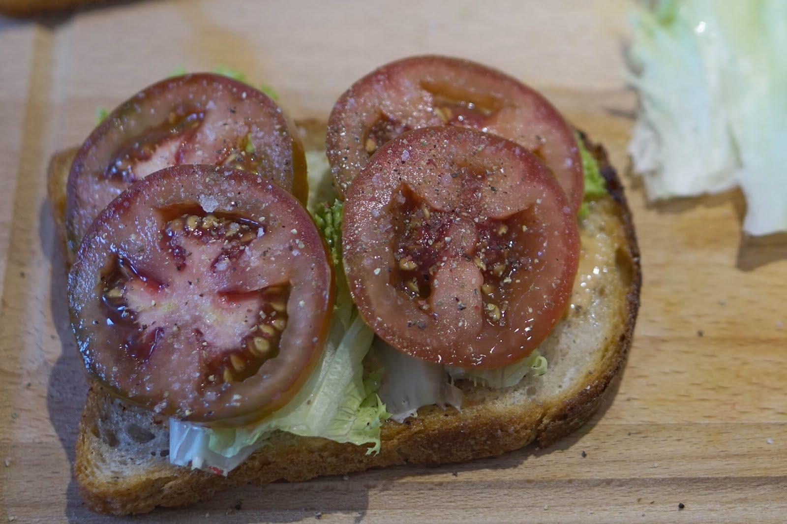 BLT Sandwich: mit Salatblätter und Tomaten belegen und würzen.