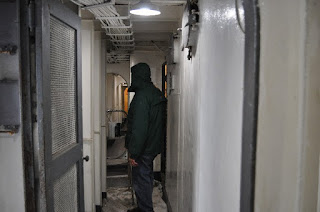 Man in Navy ship narrow hallway