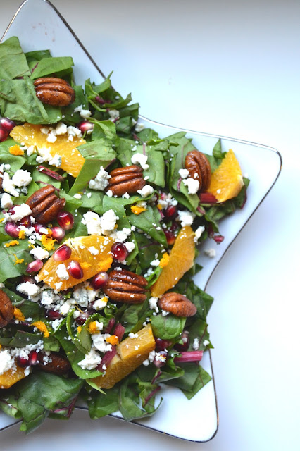 Christmas Salad- packed with Swiss chard, oranges, pomegranates, cinnamon pecans and blue cheese! www.nutritionistreviews.com