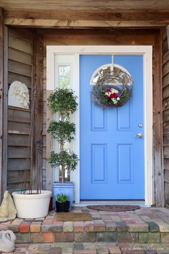 front brick porch with live floral grapevine wreath on blue front door with white trim