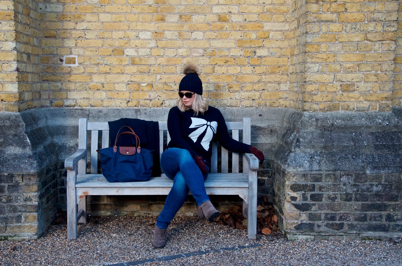 Bow sweater, jeans, boots and hat on park bench