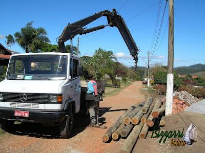 Caminhão munck preparando para chumbar os pilares de eucalipto tratado na construção da sala de estar com a suíte superior.