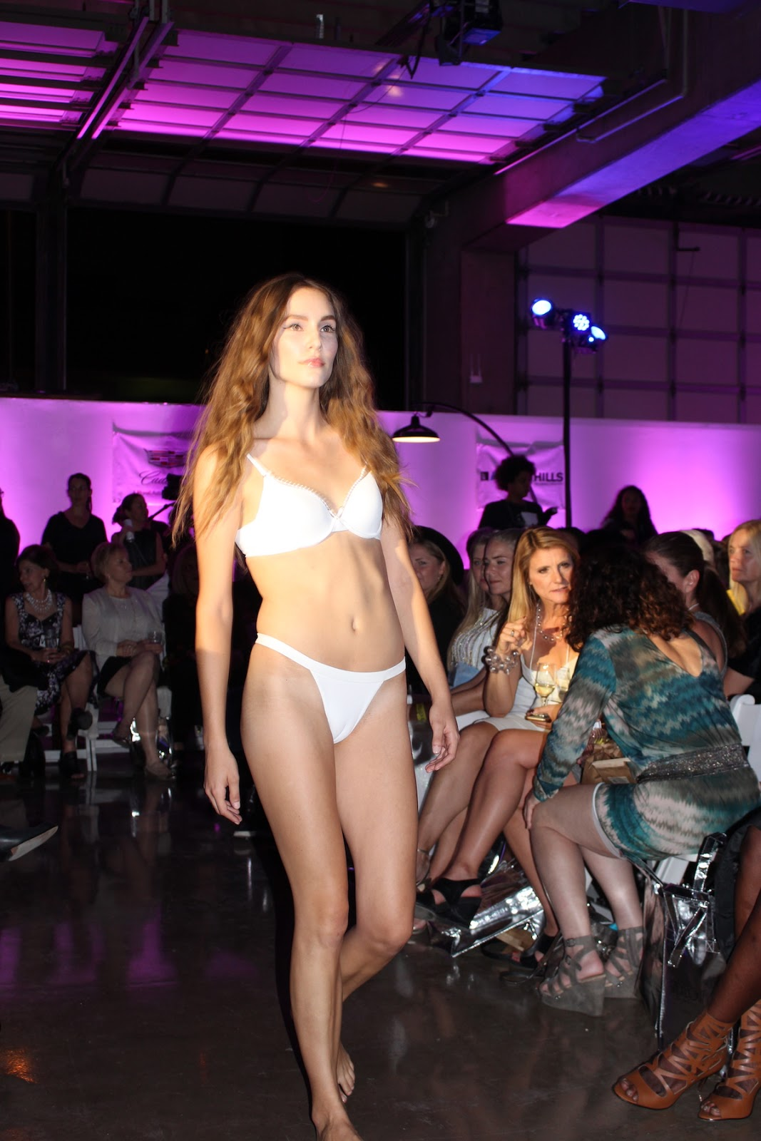 This model is strutting down the runway in a beautiful white bikini.