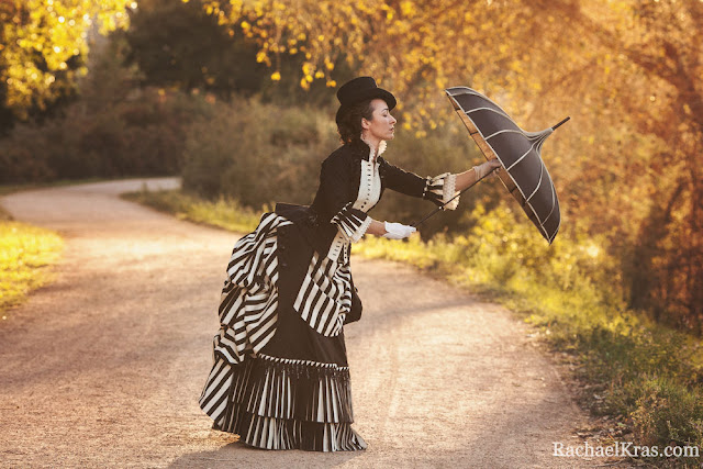 Woman wearing victorian black and white striped bustle skirt with bodice, pagoda umbrella, top hat, white gloves