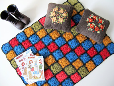 One-twelfth scale miniature 1940s afghan rug, embroidered cushions, tramping boots and paper dolls.