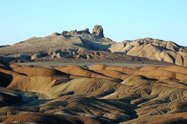 Укрытая от равнин Туркмении двумя хребтами, Сумбарская долина представляет собой единственный в своем роде уголок страны, ее субтропики. Здесь необычайно благоприятный для человека, почти не знающий зимы климат. Живительный, прозрачный воздух, напоенный ароматами трав и цветов, живописные ландшафты гор и долин — все это сближает Сумбарскую долину с Южным берегом Крыма. Лето здесь жаркое, но не изнурительно знойное, зима мягкая. Снега в долине почти не бывает, он держится только в горах и сравнительно с северными хребтами Копетдага недолго. Здесь могут расти ячмень, рожь и хлопчатник, здесь плодоносят холодостойкие сорта яблонь и теплолюбивый инжир, растут декоративные пальмы. Тенистые боковые ущелья верхней части Сумбара, орошаемые горными потоками, и особенно ущелье Айдере, густо заросли деревьями и кустарниками, среди которых много дикорастущих плодовых. Это так называемые лесосады. Ясень и платан, горный клен, барбарис и шиповник, а также яблоня, груша, грецкий орех, дикий виноград и вишня, ежевика, инжир и алыча оплетены лианами, образующими густые, подчас труднопроходимые чащи. Выше по склонам небольшими рощами растет миндаль, а в местах, хорошо освещенных солнцем и защищенных от мороза, встречаются деревца граната. Высоко в горы поднимается арча. Много любопытных достопримечательностей можно обнаружить в этой долине. Так, например, в одном из ущелий разместился прекрасный водопад Гочдемир, хрустальные струи которого кажутся ажурным занавесом, переливающимся в ярких солнечных лучах. А в окрестностях поселка Махтумкули расположились Лунные Горы. Почему «лунные»? Ответ прост: страннику действительно может показаться, что он оказался на Луне или на какой-нибудь другой, еще более загадочной планете — настолько необычен окружающий пейзаж!