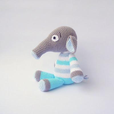 Amigurumi elephant sitting in striped pajamas