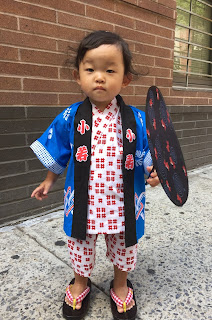Young child wearing a summer jimbe with a festival coat.