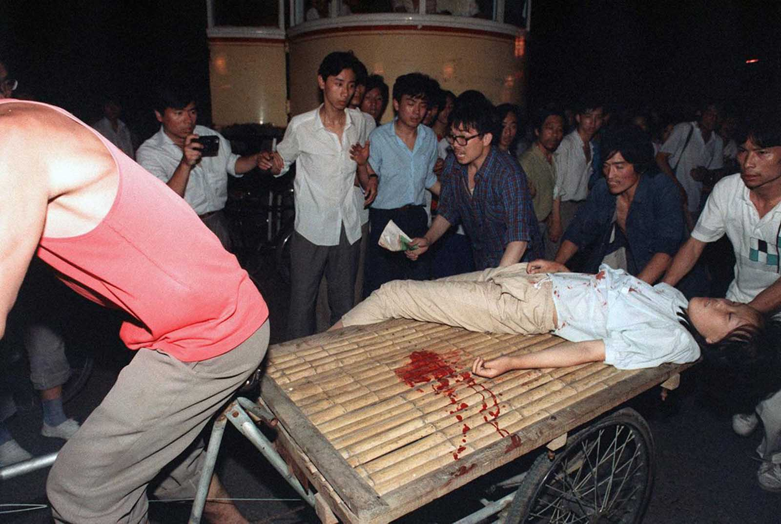 A girl wounded during the clash between the army and students near Tiananmen Square is carried out by a cart, on June 4, 1989.