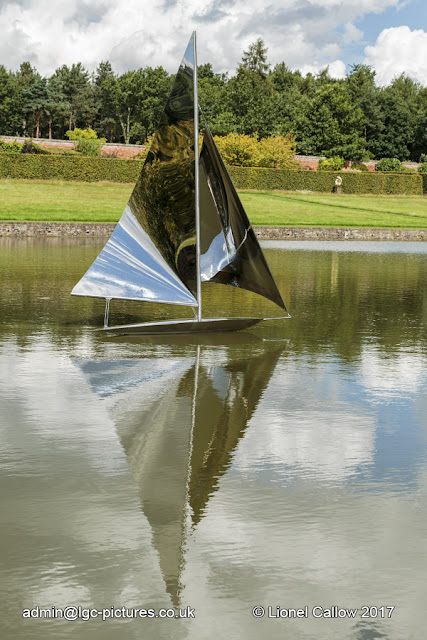 This is a stainless steel sculpture of a yacht. It is mobile with the wind floating on the lake.