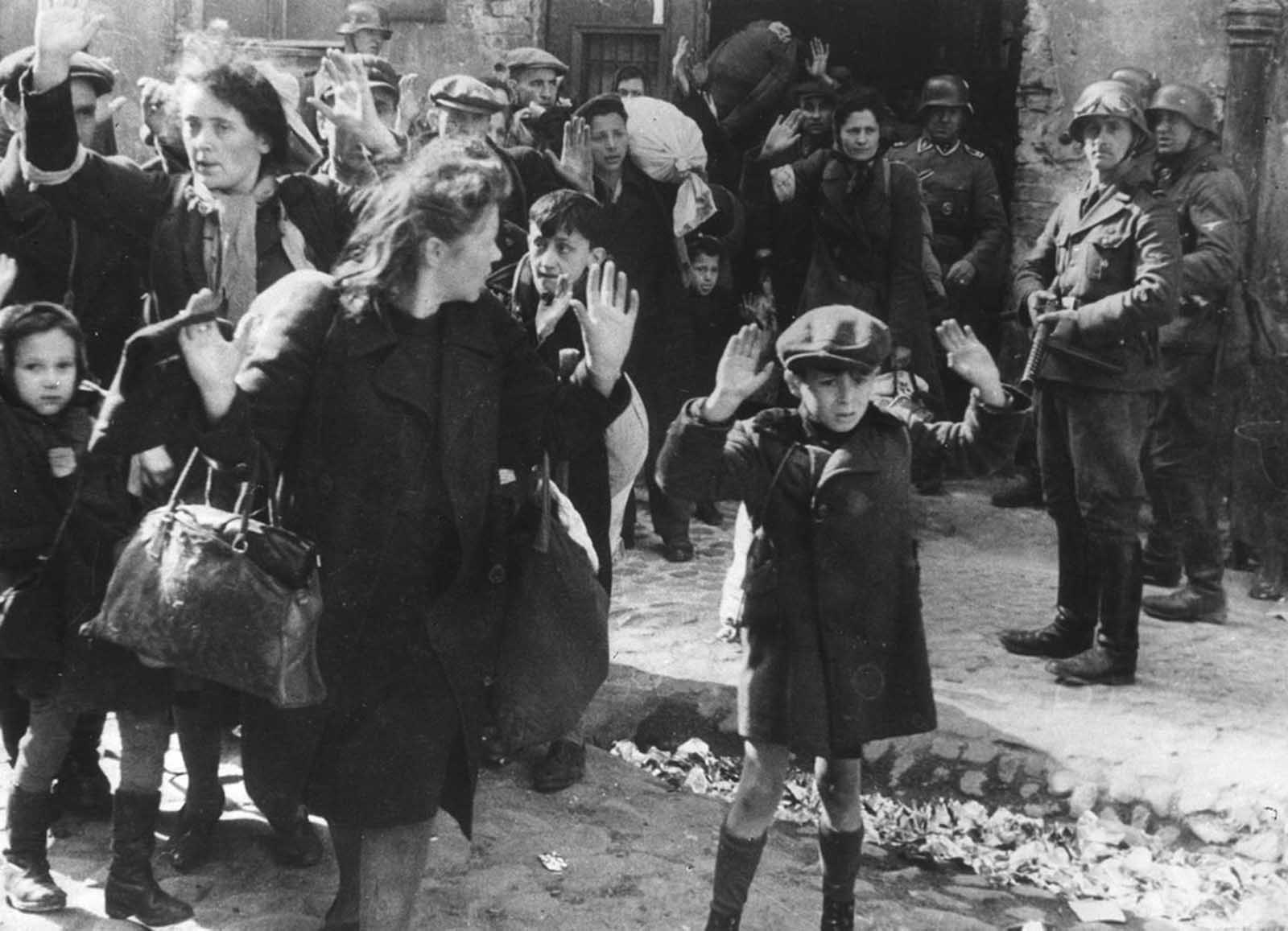 A group of Jews, including a small boy, is escorted from the Warsaw Ghetto by German soldiers in this April 19, 1943 photo. The picture formed part of a report from SS Gen. Stroop to his Commanding Officer, and was introduced as evidence to the War Crimes trials in Nuremberg in 1945.