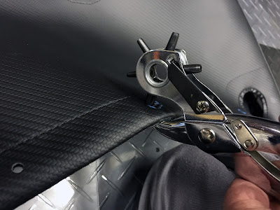 Using punch tool to cut holes into the boot cover