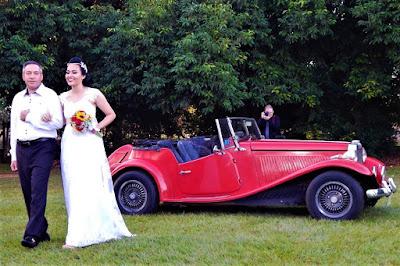 A noiva é conduzida pelo pai até o altar, após chegar no recinto num conversível.