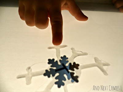 Close up of fine motor skills during snowflake light table play from And Next Comes L