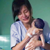 La madre sostiene a recién nacido sin vida en sus brazos, observa con atención su mano