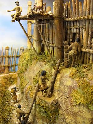 Diorama showing residents climbing up to Turuturu Mokai pa using a system of wooden logs with notches cut in them.