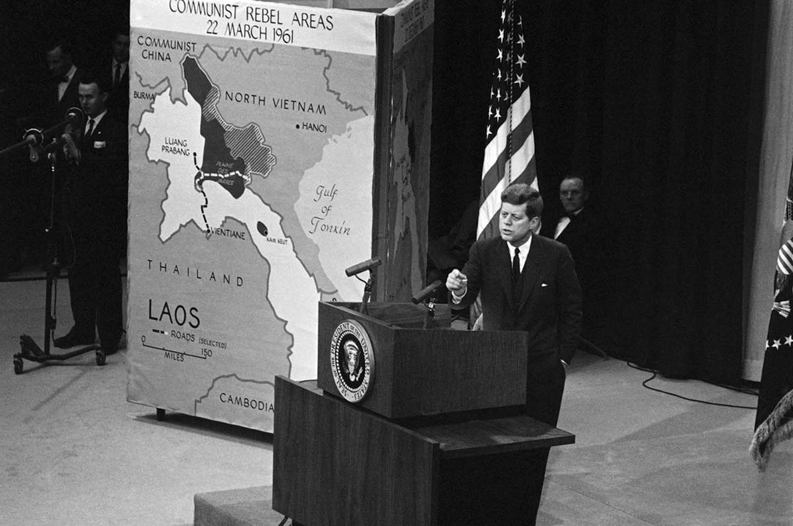 President Kennedy speaks to reporters at a nationally televised news conference in the State Department auditorium, on March 23, 1961. The Chief Executive at the opening of the conference discussed the Laos situation and used three different maps, picturing how pro-communist rebels have gained ground in the last seven months in Laos. The map at left was used by Kennedy to Show communist rebel areas as of March 22 which, he said, are indicated by the dark and shaded portions