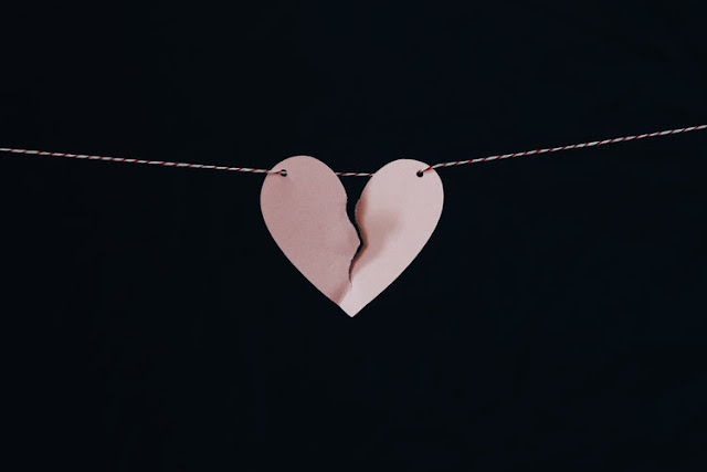 Paper heart with string threaded through, the help is torn slightly down the middle
