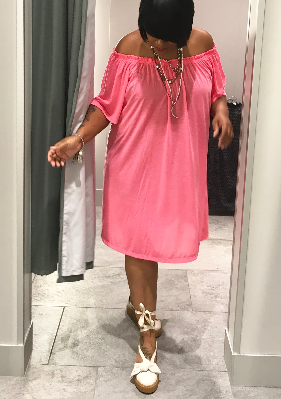 Image: Woman showing off outfit with pink details. Off the shoulder dress.