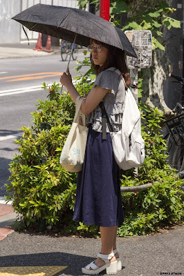 A woman underneath an umbrella on a sunny day in Tokyo.
