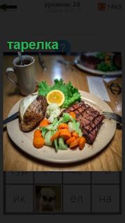 на столе стоит тарелка с едой мясо и овощи, вилка с ножом