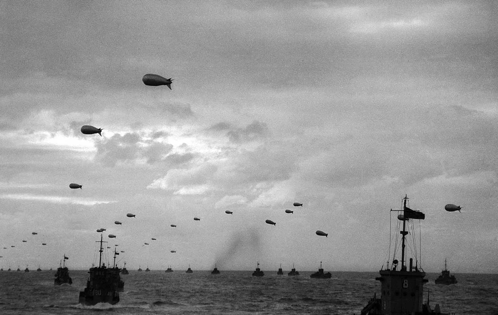 A section of the Armada of Allied landing craft with their protective barrage balloons head toward the French coast, in June of 1944.