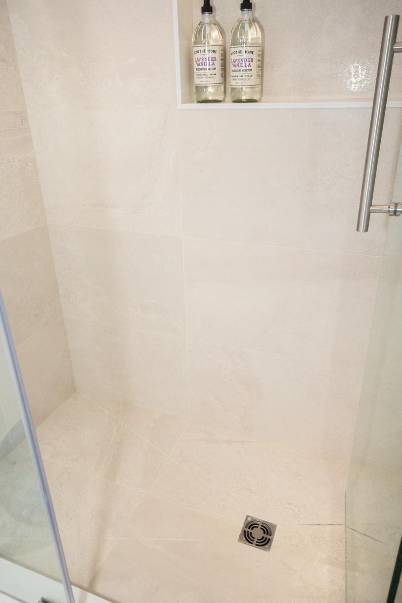 shower stall with sloped tiled floor