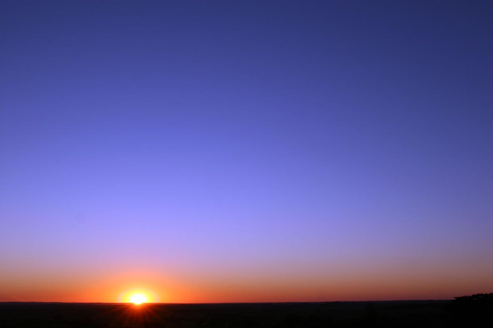 Nascer do sol, com destaque para um céu azul sem nuvens: ilustra a seção a respeito dos textos das linhas de ''Sun / A Suavidade (o Penetrante, Vento)'', um dos 64 hexagramas do I Ching, o Livro das Mutações