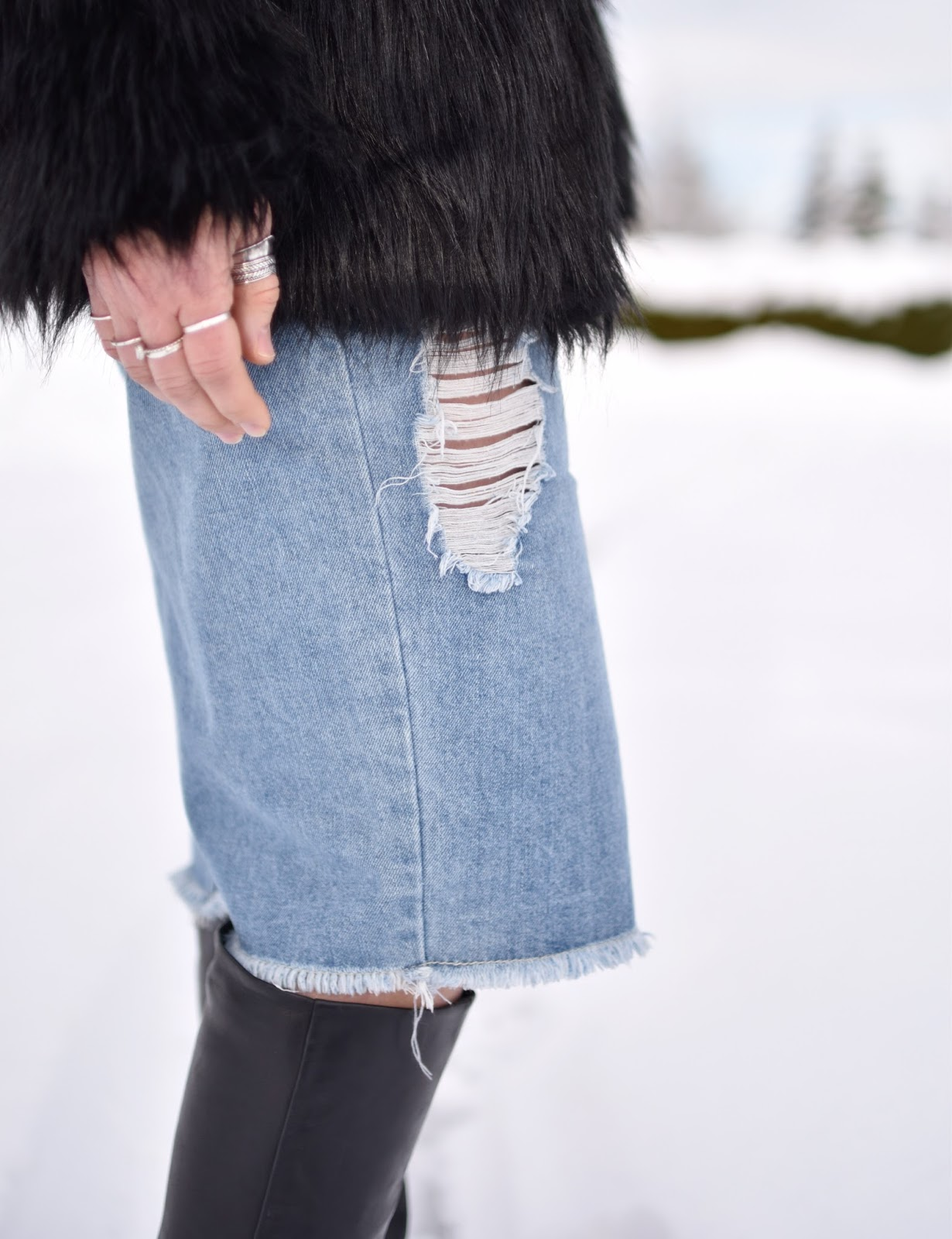 Monika Faulkner outfit inspiration - distressed denim skirt, faux-fur jacket, and black knee-high boots