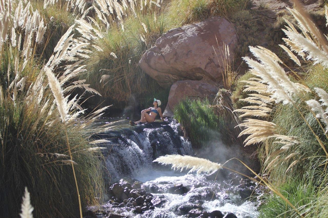 Mulher observando para cima na última piscina dos Termas de Puritama.