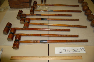 Eight wooden croquet mallets lined up on a table with yardstick - the handles are approximately on yard long, the heads of the mallets have grooves and painted stripes