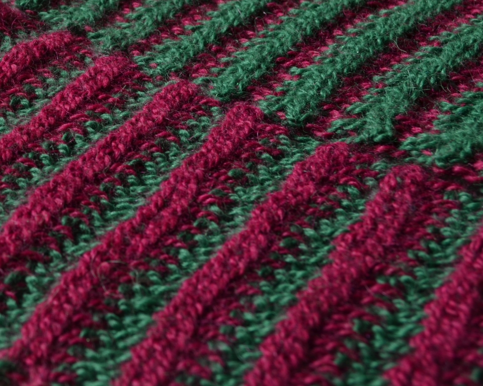 A close up of a striped scarf showing red ridges and green valleys on one side and vice versa on the other side.
