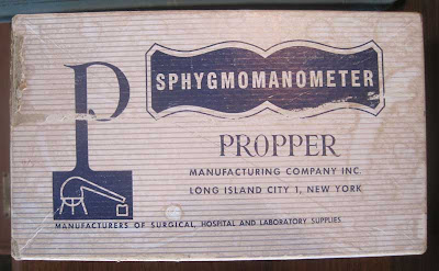 Worn paperboard box with word SPHYGMOMANOMETER on it