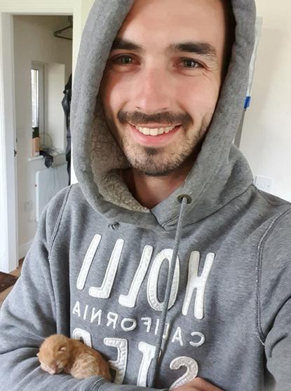 man in grey hoodie holding tiny ginger kitten