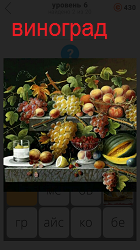 На подносе лежат фрукты и гроздья винограда
