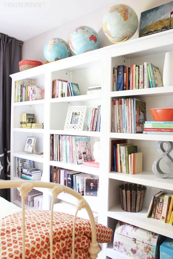 organised and lovely bookshelves with globes and colorful books