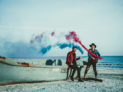 two men setting off blue and red smoke bombs beside a long canoe on the beach