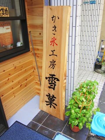 軒先に立て掛けられた屋号を印刷した木材の看板